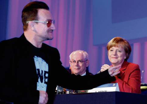 I love your early work: Bono waves to Angela Merkel and Herman Van Rompuy. Photo: Suzanne Plunkett/Reuters