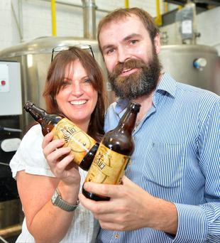 Jacqui and Ronan Kelly with their Justice craft beer at the opening of Kelly's Mountain Brew craft brewery. Photo: Adrian Melia