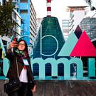 A woman takes selfies in front of the Web Summit logo on the opening day at Parque das Nacoes in Lisbon