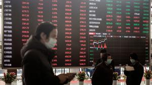 Employees and visitors wearing protective masks walk past an electronic stock board at the Shanghai Stock Exchange in Shanghai, China