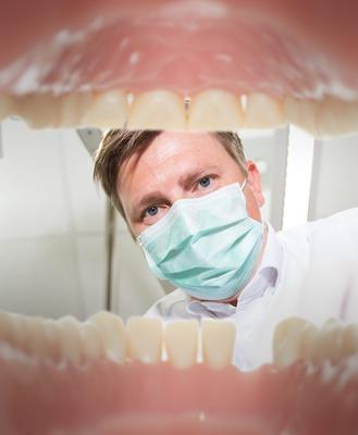 Dentist looks in to a patient's mouth.