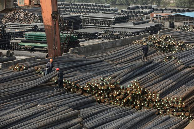 Workers stand on piles of steel rods at a depot on the outskirts of Shanghai, China — steel is one of the targets of Trump's tariffs Photo: Bloomberg