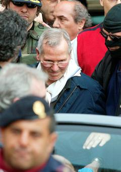 Sicilian mafia boss Bernardo Provenzano surrounded by police as he leaves the Palermo police headquarters after being arrested. Photo: Getty images