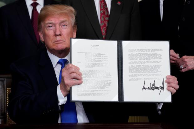 President Donald Trump holds his signed memorandum on intellectual property tariffs on high-tech goods from China.
