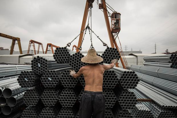 Workers lift bundles of steel pipe with a crane at a stockyard on the outskirts of Shanghai. The latest round of US tariffs has hit $34bn worth of Chinese goods. Photo: Qilai Shen/Bloomberg