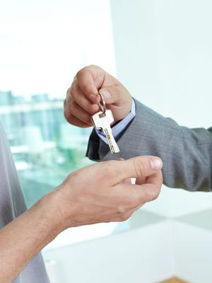 Real estate agent passing the key to the house to a satisfied male homeowner