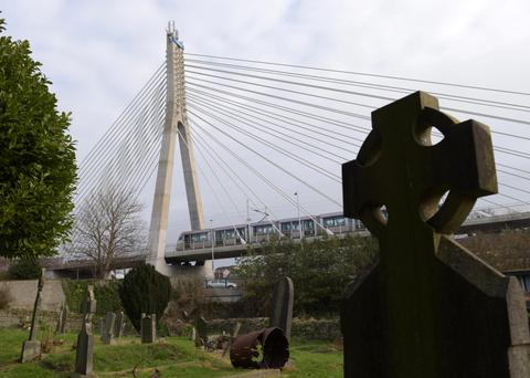 A tram on the Luas green line travels past the graveyard of St Nhai's Church in Dundrum. Photo: Bryan Meade