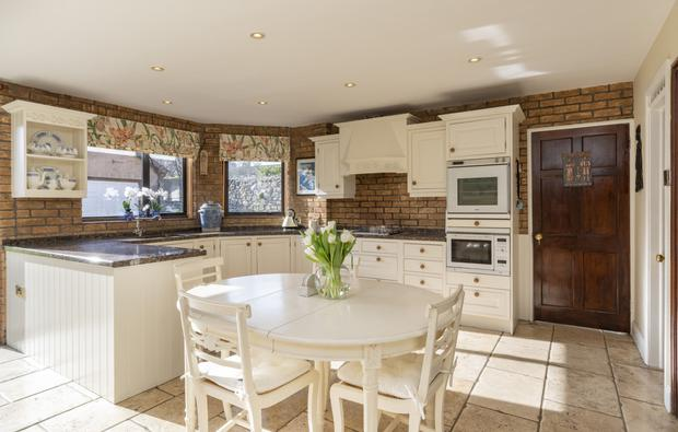 The brown bricked kitchen with white floor and eye level units