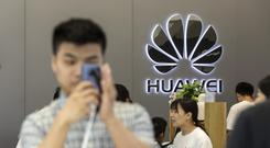 Sign of the times: An employee in front of a 5G networks sign at Huawei's headquarters in Shenzhen