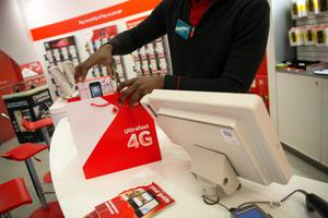 An employee places a Vodafone branded mobile handset into a shopping bag in this arranged photograph taken inside a Vodafone Group Plc store on Oxford Street in London, U.K., on Thursday, Feb. 6, 2014. Vodafone Group Chief Executive Officer Vittorio Colao is counting on growth in Asia and Africa to offset price wars in Europe. Photographer: Simon Dawson/Bloomberg