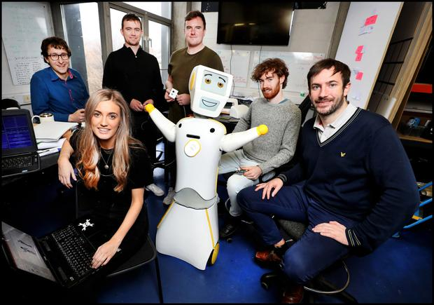 Stevie The Robot at the Robotics and Innovation Lab (RAIL) at TCD with his team (from left), Dr Michael Culligan, Niamh Donnelly, Andrew Murtagh, Eamonn Burke, Cian Donovan and Prof Conor McGinn. Photo by Steve Humphreys