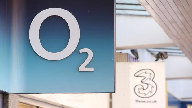 The O2 logo sits on display beyond a 3 mobile logo, outside a mobile phone store, operated by Telefonica SA, in Basildon, U.K., on Friday, Jan. 30, 2015. Rupert Murdoch's Sky Plc will offer mobile-phone services to U.K. customers through a wholesale agreement with Telefonica SA's O2, responding to a broader shake-up of the British telecommunications industry. Photographer: Chris Ratcliffe/Bloomberg