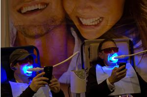 Two attendees look at their smartphones while getting their teeth whitened at the BleachBright booth at CES in Las Vegas. (AP Photo/Jae C. Hong)