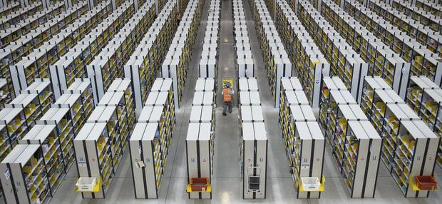 Employees push carts along aisles as they process customer orders ahead of shipping at one of Amazon.com's fulfillment centres in Rugeley, UK