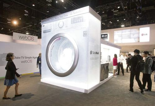 People pass by an oversize mock-up of an LG Electronics washer at the LG stand