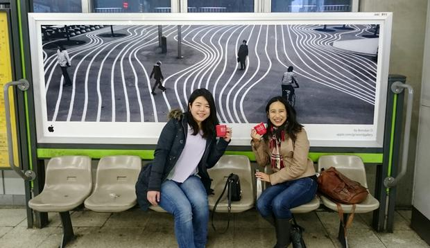 Ex UCC students Yukiho Tsunoda and Kumiko Yamaguchi in front of the Apple billboard in Tokyo featuring a photo by Brendan O Se.