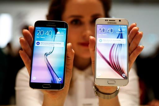An employee holds up a new Galaxy S6 Edge, left, and a Galaxy S6 smartphone device following their launch
