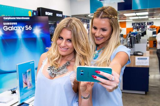 Danielle Armstrong (left) and Georgia Kousoulou from The Only Way is Essex, take a selfie with the new Samsung S6 Blue, a Carphone Warehouse exclusive, at their Stop Look Glisten selfie store at Carphone Warehouse on Oxford Street, London