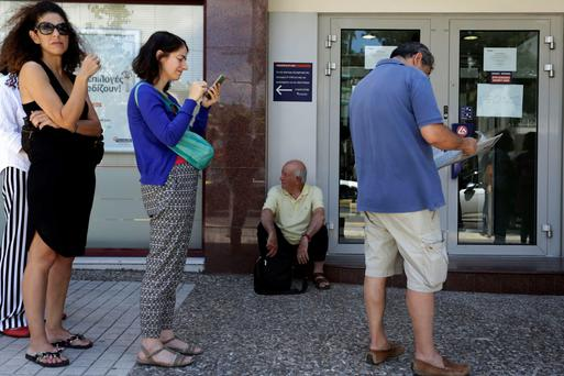 People stand in a queue as they wait to use the ATM of a bank in the Greek capital, Athens, amid the continuing uncertainty over Greece's place in the Eurozone