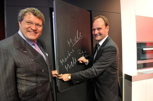 Dr Markus Miele (right) demonstrates the tech giant's high-tech blackboard fridge
