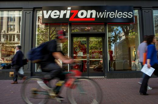 A cyclist rides past a Verizon Wireless store in San Francisco, California. Photographer: David Paul Morris/Bloomberg