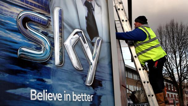 A worker erects a Sky TV poster in Birmingham, England