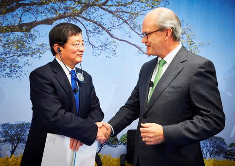 The chairman of ChemChina, Ren Jianxin, shakes hands with the chairman of Swiss farm chemicals giant Syngenta, Michel Demare, during a press conference to present Syngenta's annual results at the company's headquarters in Basel yesterday