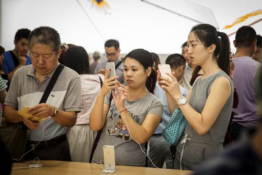 Customers look at Apple Inc.'s iPhone 6s and iPhone 6s Plus on display in Shanghai, China.