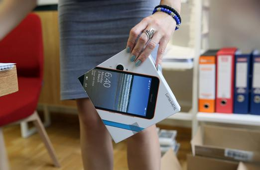 A shop worker carrying a Lumia phone model.