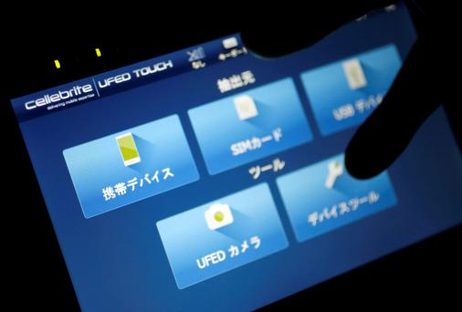 An employee of Japan's Sun Corp demonstrates Cellebrite UFED TOUCH, a device for data extraction from mobile devices