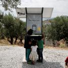 Children stand around a solar-powered charging station at the municipality-run camp of Kara Tepe on the island of Lesbos