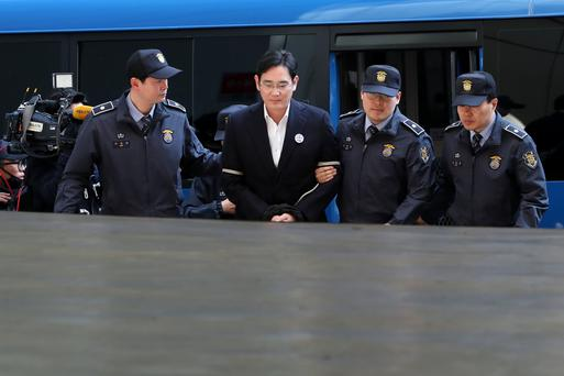 Jay Y Lee, co-vice chairman of Samsung Electronics, is escorted by police officers as he arrives at the special prosecutors' office for questioning in Seoul, South Korea