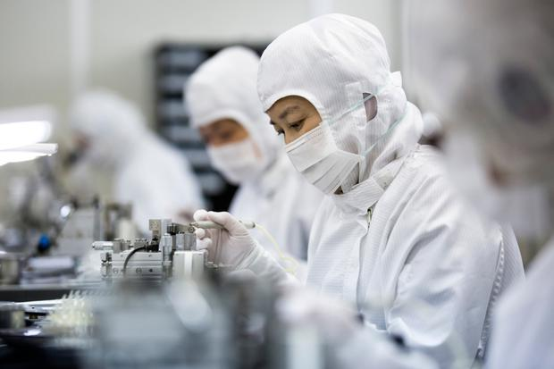 Employees assemble sample lens units for smartphones at the Kantatsu factory in Sukagawa, Fukushima, Japan