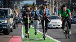 People ride electric scooters in San Francisco, California. Photo: Bloomberg