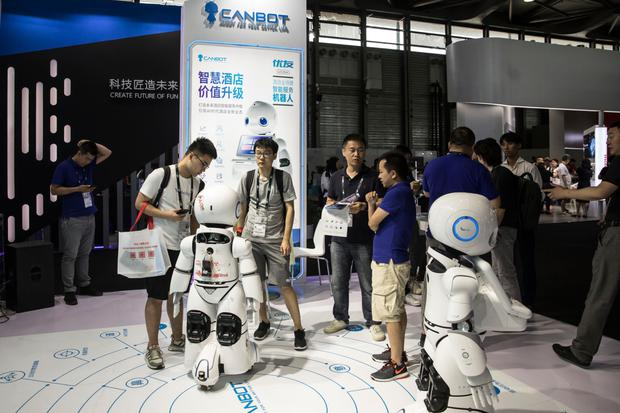 Attendees inspect robots manufactured by Beijing Kangli Youlan Robot Technology Co during the CES Asia Show in Shanghai, China. Photo: Bloomberg