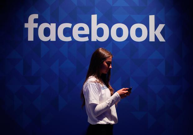 File photo dated 03/11/15 of a woman using her phone under a logo of Facebook. The social media giant has defended its security following its latest data security breach, but has been criticised for failing to apologise to users. Issue date: Wednesday April 7, 2021. PA Photo. In recent days it has emerged that personal data linked to more than 500 million Facebook accounts had been posted freely on a hacking forum, including data from about 11 million UK users. See PA story TECHNOLOGY Facebook. Photo credit should read: Niall Carson/PA Wire