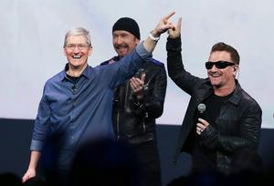 Apple CEO Tim Cook (L) greets the crowd with U2 singer Bono (R) as The Edge looks on during an Apple special event at the Flint Center for the Performing Arts
