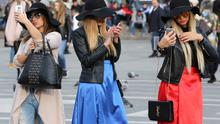 Women use their mobile phones in the industrial city of Milan. Photo: Stefano Rellandini/Reuters