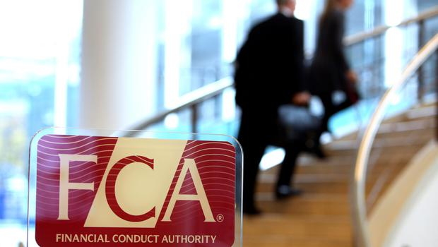 Visitors walk up a staircase as a logo sits on a sign in the reception area of the Financial Conduct Authority (FCA) in the Canary Wharf business district in London, U.K., on Thursday. Nov. 21, 2013. The FCA is working with regulators including the U.S. Department of Justice and the Commodity Futures Trading Commission to investigate the potential manipulation of the foreign-exchange market. Photographer: Chris Ratcliffe/Bloomberg