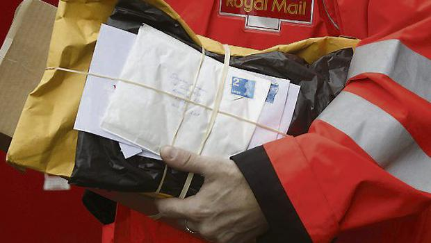 A Royal Mail Group Ltd. employee carries a bundle of letters during his delivery round in London