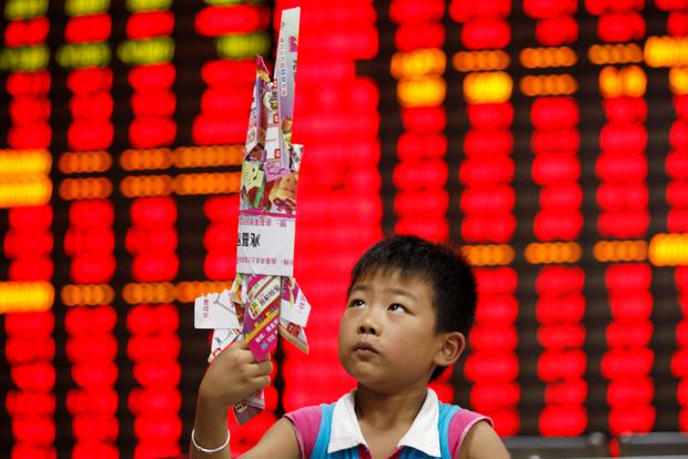 A boy plays with a toy made of paper in front of a screen showing stock information at a brokerage house in Huaibei, Anhui province. Shares closed at their highest in eight months on Monday as consumer inflation data was seen to give the Chinese authorities room to further relax monetary policy.