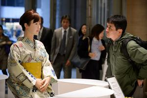 "A customer looks at humanoid robot ""Aiko Chihira"", developed by Toshiba Corp., standing at an information desk inside an Isetan Mitsukoshi Holdings Ltd. Mitsukoshi department store in Tokyo, Japan, on Monday, April 20, 2015. Prime Minister Shinzo Abe hopes to achieve a ""robot revolution"" as part of his growth strategy for a nation that's facing a shrinking workforce and declining population. Photographer: Akio Kon/Bloomberg"