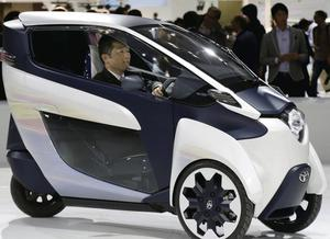 A visitor drives a three-wheeler Toyota i-ROAD electric concept car at a preview for the Tokyo Motor Show. AP