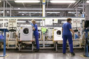 Employees check washing machine units for quality control on the production line at the Electrolux AB plant in Olawa, Poland