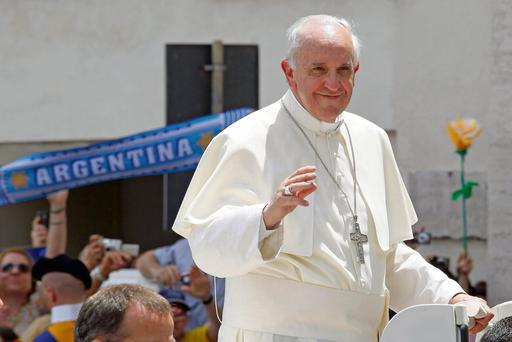 Pope Francis waves as he leaves after leading the weekly audience in Saint Peter's Square at the Vatican