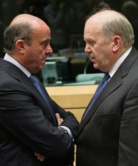 Spanish Economy Minister Luis de Guindos Jurado talks with Finance Minister Michael Noonan during the EU finance ministers meeting in Brussels which agreed a pecking order for taking losses on failed banks