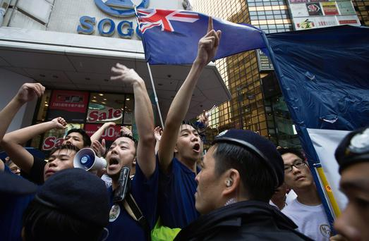 Pro-democracy protesters, with Hong Kong colonial flags, chant slogans during a protest to demand universal suffrage and urge Hong Kong's Chief Executive Leung Chun-ying to step down in Hong Kong