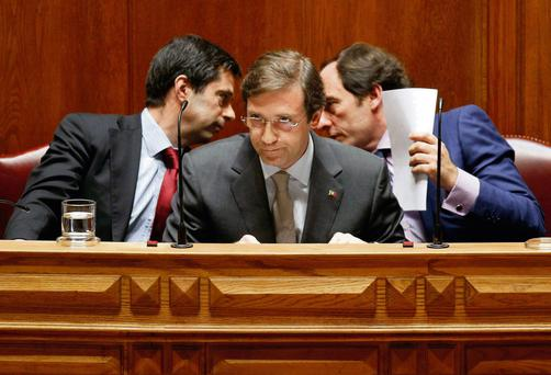 Portugal's Minister of Foreign Affairs Paulo Portas (right) talks to Finance Minister Vitor Gaspar (left), who have both resigned, behind Prime Minister Pedro Passos Coelho (centre).