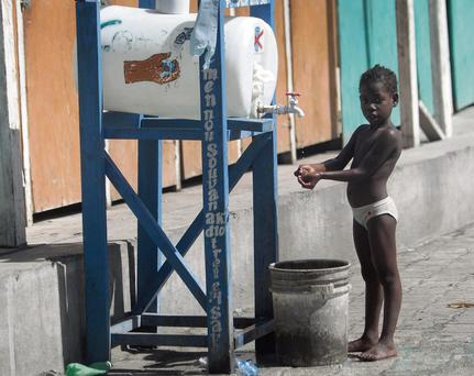 Help is at hand: A child washing at sanitation point provided by an Irish charity in Haiti