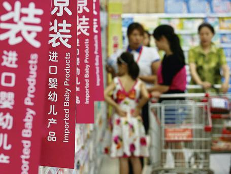 Customers shop for milk powder in front of shelves displaying imported baby products at a supermarket in Beijing. Reuters